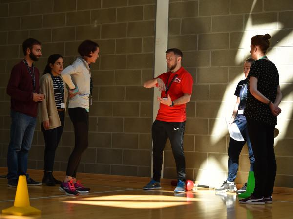 A coach addresses a group of students in a sports hall