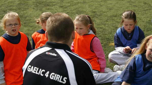 Gaelic4 Girls coach working with a group of children