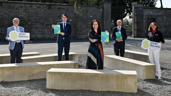 5 people standing holding a copy of the Anti Doping Review. From left to right - Kieran Mulvey, Minister Jack Chambers, Minister Catherine Martin, John Treacy, Dr. Una May